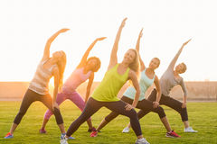 Sportiga kvinnor som värmer upp under konditiongrupp Arkivbilder