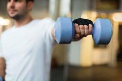 Sportiga manhänder med ljus - blåa hantlar Royaltyfria Bilder