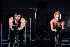 Sportiga par som övar på konditionen motionscykelen på en mörk idrottshall Royaltyfria Bilder