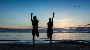 Sportiga par som gör gymnastik på havet Fotografering för Bildbyråer