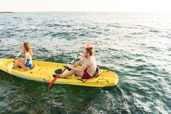 Sportiga unga par som tillsammans kaying royaltyfri foto