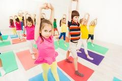 Sportiga ungar som sträcker under gymnastisk aktivitet fotografering för bildbyråer