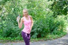 Sportigt dricksvatten för ung kvinna från flaskan Göra den utomhus- sporten arkivbilder