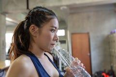Sportigt dricksvatten för ung kvinna på idrottshallen Kvinnligt drinkvatten royaltyfri fotografi