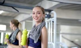 Sportigt dricksvatten för ung kvinna på idrottshallen Kvinnligt drinkvatten B arkivfoto