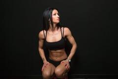 Sportigt flickasammanträde visar musklerna av hans kropp Royaltyfri Foto