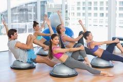 Sportigt folk som sträcker händer på yogagrupp Royaltyfri Foto