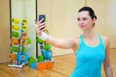 Sportigt foto för kvinnadanandeselfie på smartphonen i idrottshall arkivbild