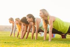 Sportigt göra för kvinnor skjuter ups under konditiongrupp Royaltyfri Bild