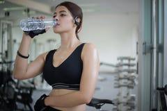 Sportigt kvinnaasia dricksvatten efter övningar i idrottshallen fit royaltyfri fotografi