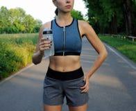 Sportigt kvinnadricksvatten från flaskan arkivbilder