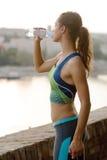 Sportigt kvinnadricksvatten som är utomhus- på solig dag Royaltyfri Fotografi