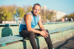 Sporting an attractive man sitting on bench and rests in the stadium. Royalty Free Stock Photography