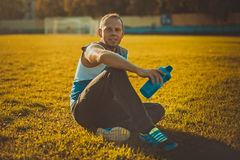 Sporting an attractive man sitting on grass and Royalty Free Stock Images