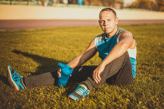 Sporting an attractive man sitting on grass. rests in the stadium and keeps shaker sunny day. Stock Images