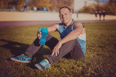 Sporting an attractive man sitting on grass. rests in the stadium and keeps shaker sunny day. Stock Photography