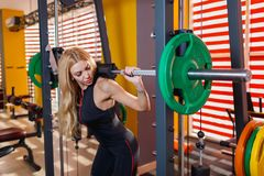 Sporting girl puts on her shoulders a heavy barbell. The concept of sport. Stock Photography