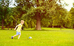 Sporting boy plays football in sunny park Stock Photos