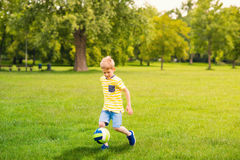 Sporting boy plays football in sunny park Stock Image