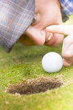 Sporting Cheat. Golfer Man Wearing Flat Cap Pulls Funny Smug Expression When Squatting Down To Give Golf Ball Flick Into The Hole In A Sporting Cheat Concept Stock Photos