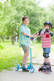 Sporting children drink water. In city park on sunny day Royalty Free Stock Photo