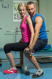 Sporting couple in the gym. Performing difficult exercises. Demonstration tense muscles. Professional athletes in training. Photos Stock Image