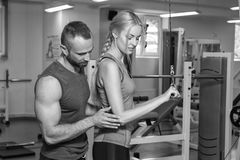 Sporting couple in the gym. Performing difficult exercises. Demonstration tense muscles. Professional athletes in training. Photos Royalty Free Stock Image