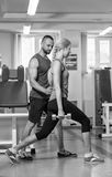 Sporting couple in the gym. Performing difficult exercises. Demonstration tense muscles. Professional athletes in training. Photos Stock Photos