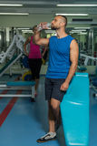 Sporting couple in the gym. Performing difficult exercises. Demonstration tense muscles. Professional athletes in training. Photos Stock Photography