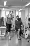 Sporting couple in the gym. Performing difficult exercises. Demonstration tense muscles. Professional athletes in training. Photos Royalty Free Stock Photos