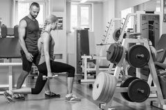 Sporting couple in the gym. Performing difficult exercises. Demonstration tense muscles. Professional athletes in training. Photos Royalty Free Stock Images