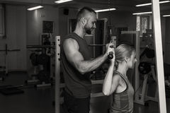Sporting couple in the gym. Performing difficult exercises. Demonstration tense muscles. Professional athletes in training. Photos Royalty Free Stock Photography