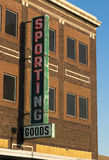Sporting Goods. An old sporting goods store sign on the side of a brick building Stock Photo