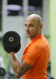 Sporting man is engaged in training in fitness center Stock Images