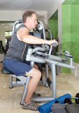 Sporting man is engaged in training in fitness center in a gym on trainers.portrait to the utmost Stock Photography
