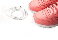 Sporting pink sneakers on a white background with headphones. Training. Sport. And Stock Photos