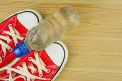 Sporting red shoes on a wooden background with a bottle of water Royalty Free Stock Photo