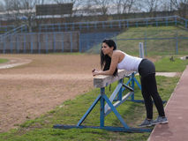 After sporting. Sporting and shapely black haired woman rely on sports equipment Royalty Free Stock Images