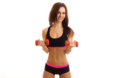 Sporting a slender brunette with press stands in short shorts is smiling and holding a dumbbell Stock Photography