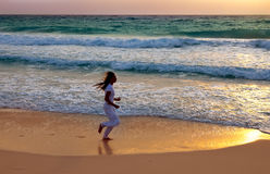 Sporting woman in beach. Sporting woman is engaged in run on the sea coast on a beach Stock Images