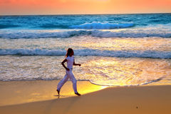Sporting woman is engaged in run on the sea coast on a beach.Sea tropical landscape Royalty Free Stock Photo
