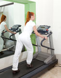 Sporting woman in fitness center trains Stock Photography