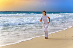 Sporting woman  run on the sea coast on a beach on a sunset Royalty Free Stock Photo
