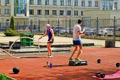 Sporting young men doing some crossfit exercises with ropes outdoors. Saint-Petersburg. Russia. 05.19.2018.Sports young people do some crossfit exercises with Royalty Free Stock Images