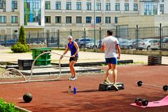 Sporting young men doing some crossfit exercises with ropes outdoors. Saint-Petersburg. Russia. 05.19.2018. Sports young people do some crossfit exercises with Royalty Free Stock Photos