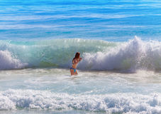 The sporting young woman in big waves Stock Photos