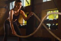 Sportiva adatta, sportiva ed atletica che lavora in una palestra Addestramento della donna facendo uso delle corde di battaglia S fotografia stock