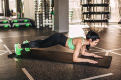 Sportiva adulta esile in plancia sulla stuoia fotografia stock