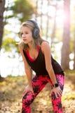 sportiva attraente che ascolta le cuffie d'uso di musica e che controlla il suo orologio astuto Sport, forma fisica, concetto di  immagini stock libere da diritti