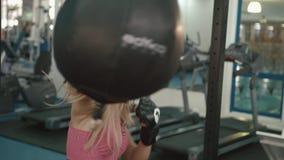 Sportiva bionda attraente che risolve inscatolando un punching ball alla palestra moderna 4K archivi video